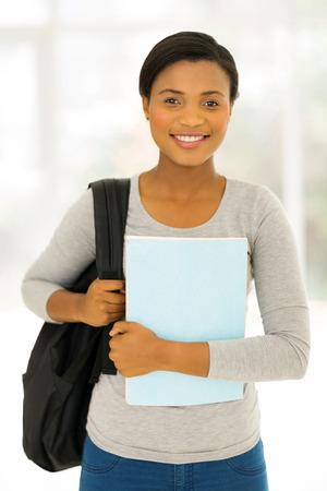 MOCHILA: mujer atractiva estudiante afroamericana que sostiene un libro en casa