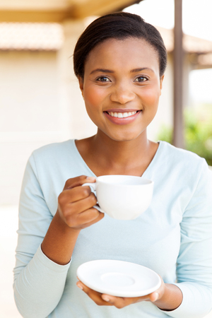 black lady: portrait of young african woman drinking coffee at home