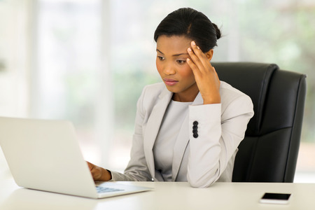 thoughtful african businesswoman looking at laptop screen in modern office