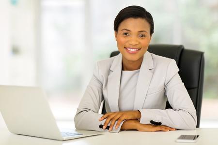 relajado: sonriendo empresaria afroamericana de trabajo en la oficina