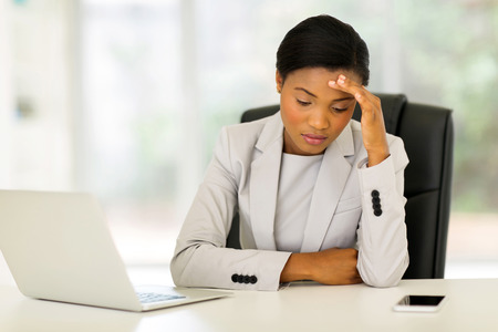 stressed african businesswoman sitting in office Stockfoto