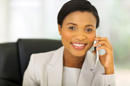 attractive businesswoman: happy african businesswoman talking on mobile phone in office