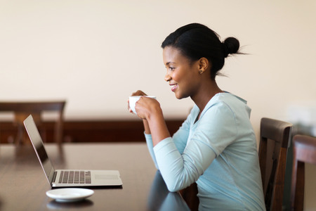 happy black woman: beautiful young african woman drinking coffee while using laptop at home