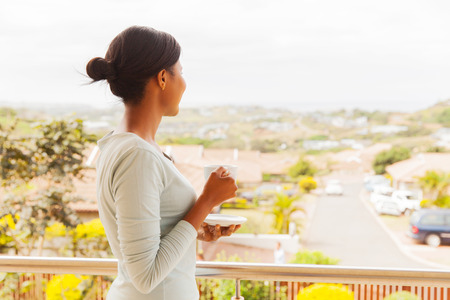 back view of african woman drinking tea on balcony
