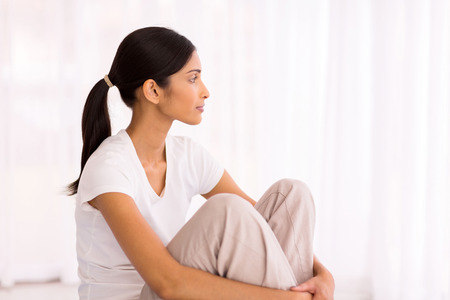 woman thinking: thoughtful young indian woman sitting in her new apartment