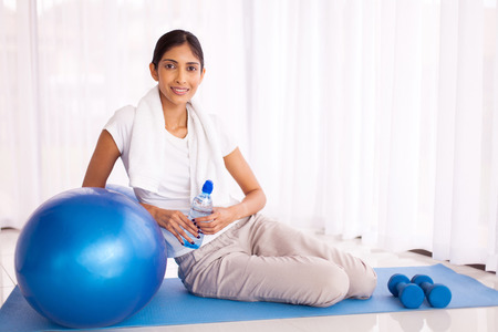 woman in towel: portrait of indian woman sitting on mat with exercise ball