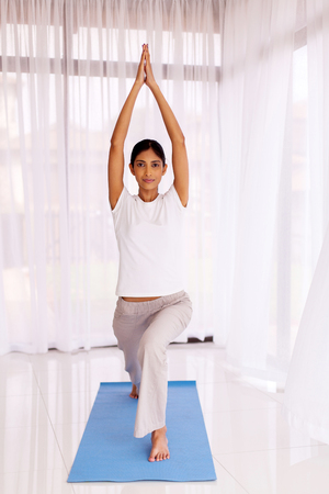 indian yoga: pretty young indian woman doing fitness stretching at home