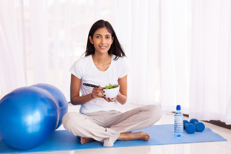 indian yoga: attractive indian woman eating healthy salad on yoga mat