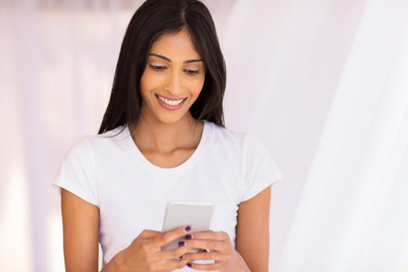 cheerful young indian woman using smart phone at home