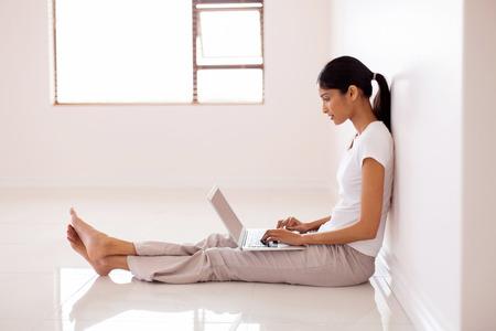 descansando: joven India trabaja en el ordenador port�til en casa nueva Foto de archivo