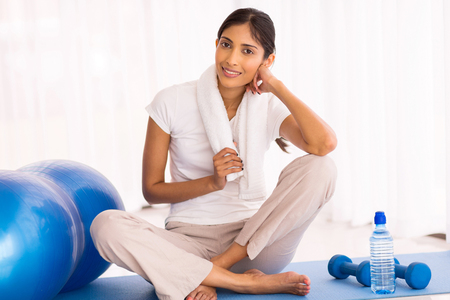 indian ethnicity: attractive young indian woman sitting on exercise mat at home Stock Photo