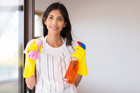 window cleaning: portrait of happy young indian woman doing housework Stock Photo