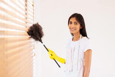 ウィンドウをクリーニングかなり若いインド人女性の羽の塵払いのブラインドします。 写真素材