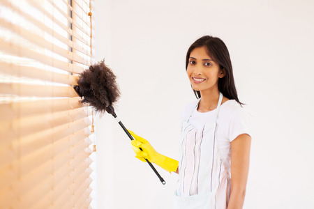 pretty young indian woman cleaning window blinds with feather duster