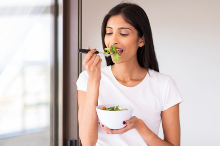 healthy indian woman eating green salad