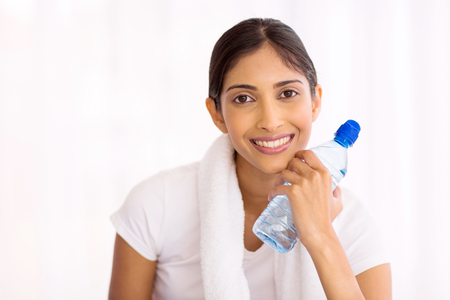 ball of water: healthy fitness indian woman with water bottle after exercise at home