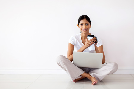 girl with laptop: beautiful young indian woman holding coffee mug at home