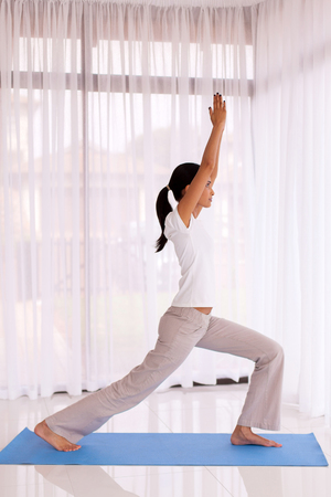 indian yoga: side view of fit indian woman doing yoga pose indoors Stock Photo