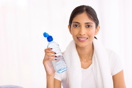 woman in water: fit young indian woman drinking water after exercising indoors Stock Photo