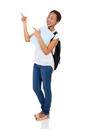 cheerful: cheerful young african university student pointing on white background