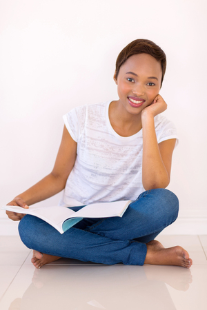 female student: smart african american college student reading a book at home