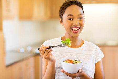 woman eat: cheerful young afro american woman eating vegetable salad in home kitchen Stock Photo