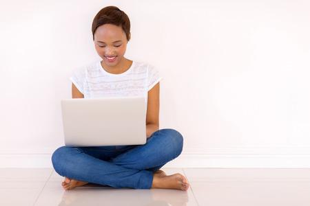 persona sentada: joven y bella mujer africana leer mensajes de correo electrónico en la computadora portátil en casa