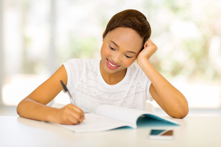 african student: beautiful african college student writing homework at home