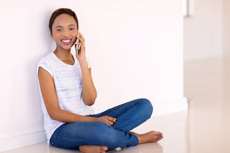 mujeres sentadas: relajada mujer joven negro hablando por teléfono celular