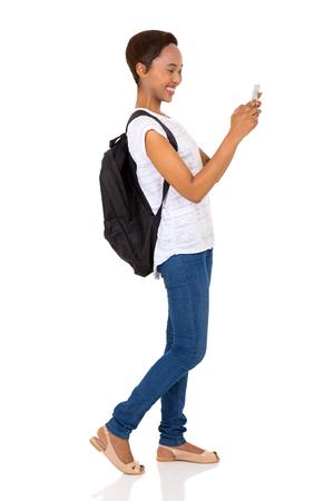 using phone: cheerful african university student using smart phone isolated on white background