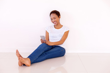 women sitting: happy african american woman using smart phone at home Stock Photo