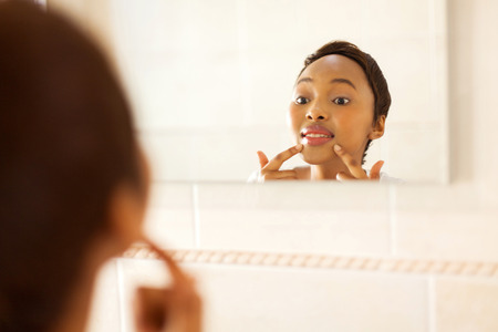 beautiful young african woman checking for pimple on her face Stock Photo