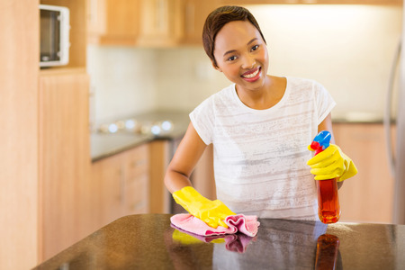 cleaning products: beautiful young african woman doing house chores