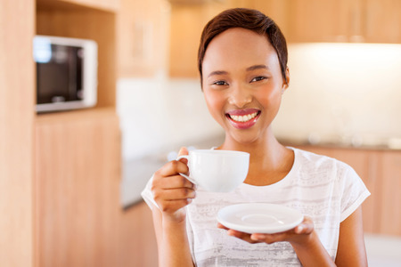 drinking tea: pretty young african woman drinking coffee in kitchen Stock Photo