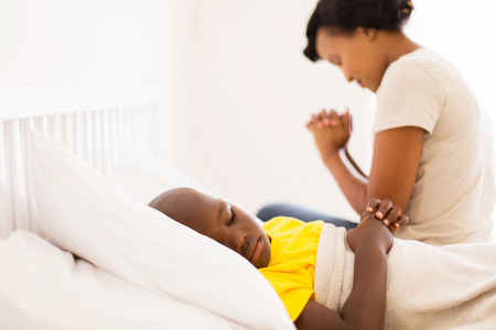 praying people: african sick little boy lying in bed with his mother praying on background Stock Photo