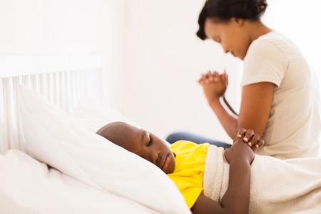 familia orando: africano niño pequeño enfermo en la cama con su madre rezando en el fondo