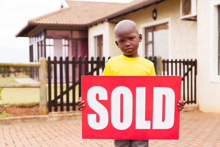 child holding sign: little african boy standing outside the house and holding sold sign
