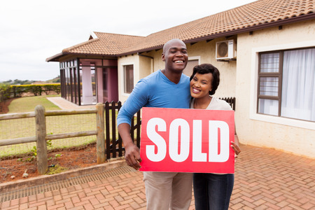 sold sign: happy african couple standing outside their house and holding sold sign Stock Photo