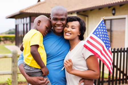 アメリカの国旗を保持している美しいアフリカ系アメリカ人の家族