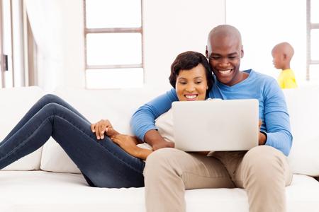 Gelukkig Afro-Amerikaanse echtpaar met behulp van laptop thuis met hun zoon op de achtergrond Stockfoto