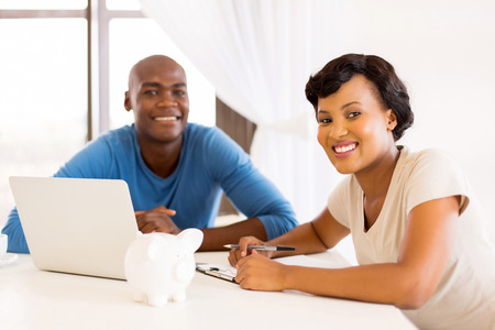 finance girl: smart young african couple  doing their financials or paying bills