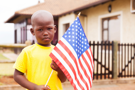 patriotic: portrait of adorable little boy holding american flag in front of house