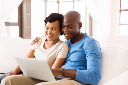 using computer: modern young african american couple using laptop computer at home