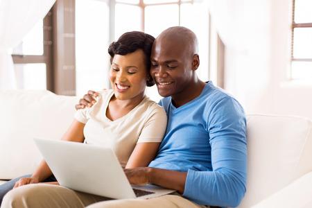 usando computadora: Moderna pareja joven africano utilizando equipo portátil en casa