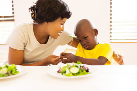african family: beautiful african mother asking her son to eat vegetables Stock Photo