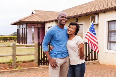 feliz casal americano africano que prende a bandeira dos EUA fora de sua casa