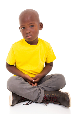 sad african american boy sitting on white background