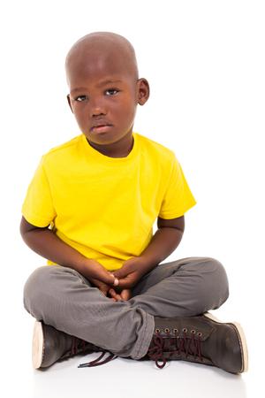 sad african american boy sitting on white background