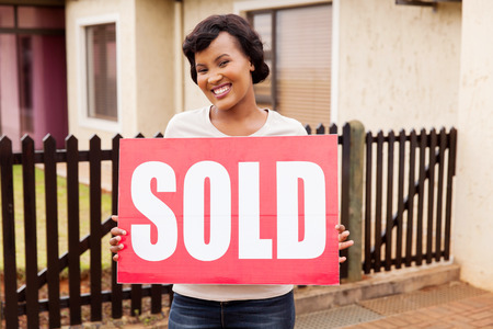 african american woman: cheerful african american woman holding sold sign outside her house