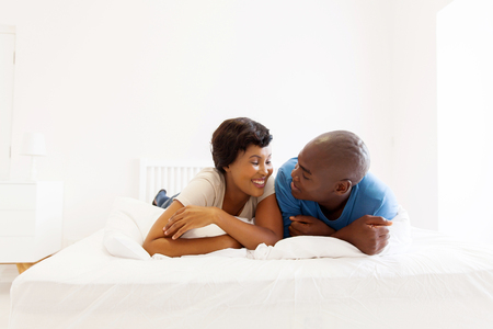 pareja amor: lovely african american couple lying on bed Foto de archivo